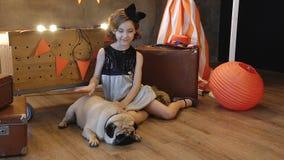 Συνεδρίαση μικρών κοριτσιών κοντά σε αναδρομικό μια βαλίτσα με το σκυλί απόθεμα βίντεο