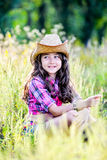 Συνεδρίαση μικρών κοριτσιών σε έναν τομέα που φορά ένα καπέλο κάουμποϋ Στοκ Εικόνες