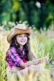 Συνεδρίαση μικρών κοριτσιών σε έναν τομέα που φορά ένα καπέλο κάουμποϋ Στοκ φωτογραφία με δικαίωμα ελεύθερης χρήσης