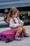 Συνεδρίαση μικρών κοριτσιών στη βαλίτσα στο σιδηροδρομικό σταθμό με το τραίνο στο υπόβαθρο Στοκ εικόνα με δικαίωμα ελεύθερης χρήσης