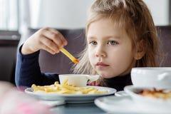 Συνεδρίαση μικρών κοριτσιών στον πίνακα και κατανάλωση των τηγανιτών πατατών Στοκ εικόνες με δικαίωμα ελεύθερης χρήσης