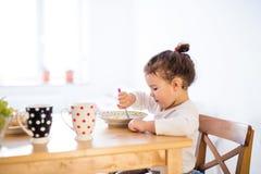 Συνεδρίαση μικρών κοριτσιών στον πίνακα, που τρώει το πρόγευμα Στοκ εικόνα με δικαίωμα ελεύθερης χρήσης