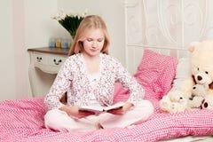 Συνεδρίαση μικρών κοριτσιών στο κρεβάτι που διαβάζει ένα βιβλίο Στοκ Εικόνα