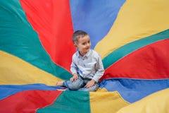 συνεδρίαση μικρών παιδιών αγοριών παιδιών στο κέντρο του αλεξίπτωτου ουράνιων τόξων παιδικών χαρών Στοκ φωτογραφίες με δικαίωμα ελεύθερης χρήσης