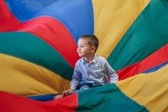 συνεδρίαση μικρών παιδιών αγοριών παιδιών στο κέντρο του αλεξίπτωτου ουράνιων τόξων παιδικών χαρών Στοκ Φωτογραφίες