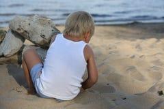 Συνεδρίαση μικρών παιδιών στην άμμο στην παραλία κοντά στον ποταμό Στοκ Φωτογραφίες
