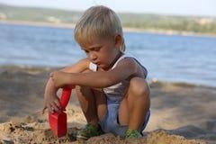 Συνεδρίαση μικρών παιδιών στην άμμο στην παραλία κοντά στον ποταμό Στοκ εικόνα με δικαίωμα ελεύθερης χρήσης