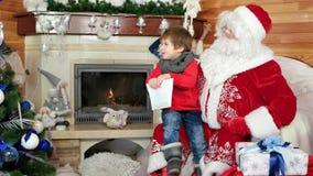 Συνεδρίαση μικρών παιδιών στην περιτύλιξη santa ` s, παιδί που επισκέπτεται τη χειμερινή κατοικία Αγίου Nicolas με την επιστολή h απόθεμα βίντεο