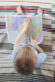 Συνεδρίαση μικρών παιδιών στον καναπέ και υπόδειξη στο χάρτη Στοκ εικόνα με δικαίωμα ελεύθερης χρήσης
