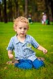 Συνεδρίαση μικρών παιδιών στο χορτοτάπητα Στοκ φωτογραφία με δικαίωμα ελεύθερης χρήσης