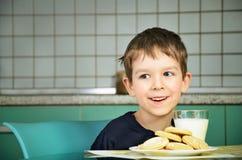 Συνεδρίαση μικρών παιδιών χαμόγελου εύθυμη στον πίνακα γευμάτων horizo Στοκ Εικόνα