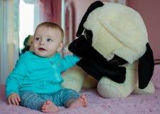 Συνεδρίαση μωρών με το μεγάλο σκυλί παιχνιδιών Στοκ φωτογραφία με δικαίωμα ελεύθερης χρήσης