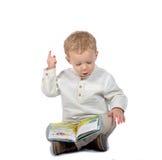 Συνεδρίαση μωρών που διαβάζει cross-legged ένα βιβλίο Στοκ εικόνες με δικαίωμα ελεύθερης χρήσης