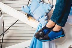 Συνεδρίαση μωρών σε μια άσπρη ρόδα που φορά το τζιν παντελόνι και τα μαύρα παπούτσια Στοκ Εικόνες