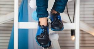 Συνεδρίαση μωρών σε μια άσπρη ρόδα που φορά το τζιν παντελόνι και τα μαύρα παπούτσια Στοκ φωτογραφία με δικαίωμα ελεύθερης χρήσης