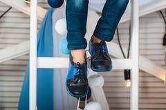 Συνεδρίαση μωρών σε μια άσπρη ρόδα που φορά το τζιν παντελόνι και τα μαύρα παπούτσια Στοκ Φωτογραφία