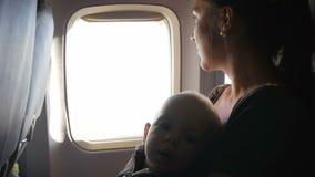 Συνεδρίαση μωρών στην περιτύλιξη της μητέρας σε ένα αεροπλάνο κατά τη διάρκεια της πτήσης Κοιτάζει γύρω από και σχετικά με τη ζών φιλμ μικρού μήκους