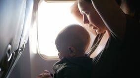 Συνεδρίαση μωρών στην περιτύλιξη της μητέρας σε ένα αεροπλάνο κατά τη διάρκεια της πτήσης Κοιτάζει γύρω από και σχετικά με τη ζών απόθεμα βίντεο