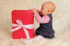 Συνεδρίαση μωρών besid ένα δώρο Στοκ φωτογραφίες με δικαίωμα ελεύθερης χρήσης