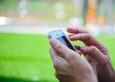 Συνεδρίαση νέων κοριτσιών στην πράσινη χλόη με το κινητό τηλέφωνο χρησιμοποίηση γυναικών Στοκ Φωτογραφία