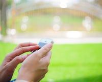 Συνεδρίαση νέων κοριτσιών στην πράσινη χλόη με το κινητό τηλέφωνο Στοκ Φωτογραφίες