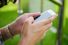 Συνεδρίαση νέων κοριτσιών στην πράσινη χλόη με το κινητό τηλέφωνο Στοκ φωτογραφία με δικαίωμα ελεύθερης χρήσης