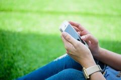 Συνεδρίαση νέων κοριτσιών στην πράσινη χλόη με το κινητό τηλέφωνο Στοκ φωτογραφίες με δικαίωμα ελεύθερης χρήσης
