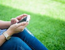 Συνεδρίαση νέων κοριτσιών στην πράσινη χλόη με το κινητό τηλέφωνο Στοκ εικόνα με δικαίωμα ελεύθερης χρήσης