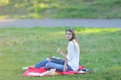 Συνεδρίαση νέων κοριτσιών στη χλόη στο πάρκο και εργασίες σε ένα lap-top και την κατανάλωση του γρήγορου φαγητού Στοκ φωτογραφία με δικαίωμα ελεύθερης χρήσης