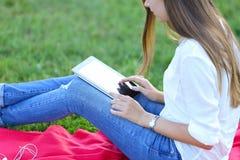 Συνεδρίαση νέων κοριτσιών στη χλόη στο πάρκο και εργασίες σε ένα lap-top και την κατανάλωση του γρήγορου φαγητού Στοκ Φωτογραφίες