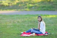Συνεδρίαση νέων κοριτσιών στη χλόη στο πάρκο και εργασίες σε ένα lap-top και την κατανάλωση του γρήγορου φαγητού Στοκ Εικόνες