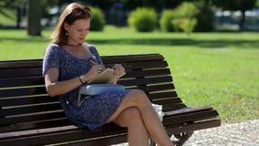 Συνεδρίαση νέων κοριτσιών στον πάγκο σε ένα πάρκο και φιλμ μικρού μήκους