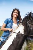Συνεδρίαση νέων κοριτσιών στο άλογο ενάντια στο μπλε ουρανό Στοκ φωτογραφία με δικαίωμα ελεύθερης χρήσης