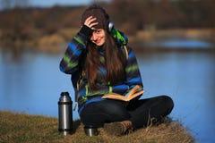 Συνεδρίαση νέων κοριτσιών στο έδαφος και χαλάρωση με το βιβλίο Στοκ Εικόνες