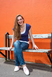 Συνεδρίαση νέων κοριτσιών χαμόγελου όμορφη σε έναν ηλιόλουστο πάγκο κολλεγίων Στοκ φωτογραφία με δικαίωμα ελεύθερης χρήσης