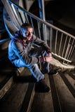 Συνεδρίαση νεαρών άνδρων στα αστικά σκαλοπάτια τη νύχτα στοκ εικόνα