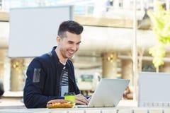 Συνεδρίαση νεαρών άνδρων στον καφέ με την εργασία καφέ και σάντουιτς Στοκ εικόνες με δικαίωμα ελεύθερης χρήσης