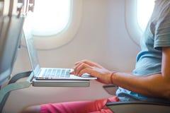 Συνεδρίαση νεαρών άνδρων στο αεροπλάνο και εργασία στο lap-top του στοκ εικόνα