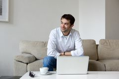 Συνεδρίαση νεαρών άνδρων στο σπίτι με το lap-top Στοκ Φωτογραφία