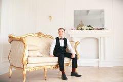 Συνεδρίαση νεόνυμφων στον καναπέ που περιμένει τη νύφη στη ημέρα γάμου του στο γαμήλιο σμόκιν που χαμογελά και που περιμένει τη ν Στοκ Εικόνες