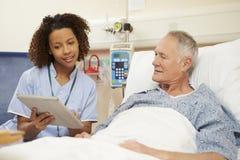 Συνεδρίαση νοσοκόμων από το κρεβάτι του αρσενικού ασθενή που χρησιμοποιεί την ψηφιακή ταμπλέτα στοκ εικόνες