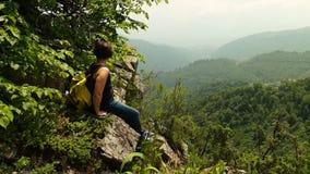 Συνεδρίαση οδοιπόρων γυναικών στον απότομο βράχο στα βουνά απόθεμα βίντεο