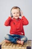 Συνεδρίαση παιδιών με τα διασχισμένα πόδια και άκουσμα στη μουσική Στοκ εικόνες με δικαίωμα ελεύθερης χρήσης