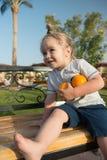 Συνεδρίαση παιδιών με δύο πορτοκάλια στον πάγκο Στοκ φωτογραφία με δικαίωμα ελεύθερης χρήσης