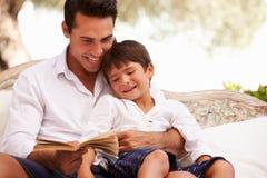 Συνεδρίαση πατέρων και γιων στο βιβλίο ανάγνωσης κήπων από κοινού Στοκ Φωτογραφίες