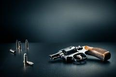 Συνεδρίαση πυροβόλων όπλων σε έναν πίνακα με τα κοχύλια σφαιρών/το δραματικό φωτισμό Στοκ εικόνες με δικαίωμα ελεύθερης χρήσης