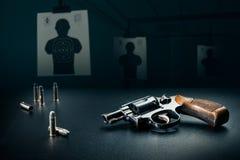 Συνεδρίαση πυροβόλων όπλων σε έναν πίνακα σε μια σειρά πυροβολισμού/έναν δραματικό φωτισμό Στοκ φωτογραφία με δικαίωμα ελεύθερης χρήσης