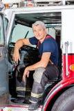 Συνεδρίαση πυροσβεστών χαμόγελου αρσενική στο φορτηγό Στοκ εικόνα με δικαίωμα ελεύθερης χρήσης