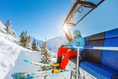 Συνεδρίαση σκιέρ στον ανελκυστήρα καρεκλών σκι στα αλπικά βουνά Στοκ Εικόνα