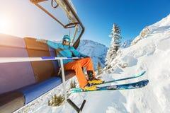 Συνεδρίαση σκιέρ στον ανελκυστήρα καρεκλών σκι στα αλπικά βουνά Στοκ φωτογραφία με δικαίωμα ελεύθερης χρήσης